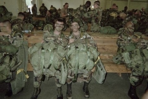 A picture of me and my friend in the pack shed before loading a plane to jump. We are sitting on a bench in full jump gear. Counting the parachutes & our equipment we were typically jumping with 120-150lbs of equipment on us. I usually jumped with a radio in my ruck sack.
